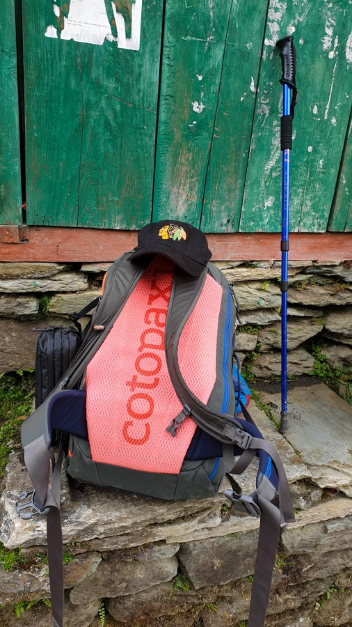 A backpack, walking stick and a cap next to a house wall