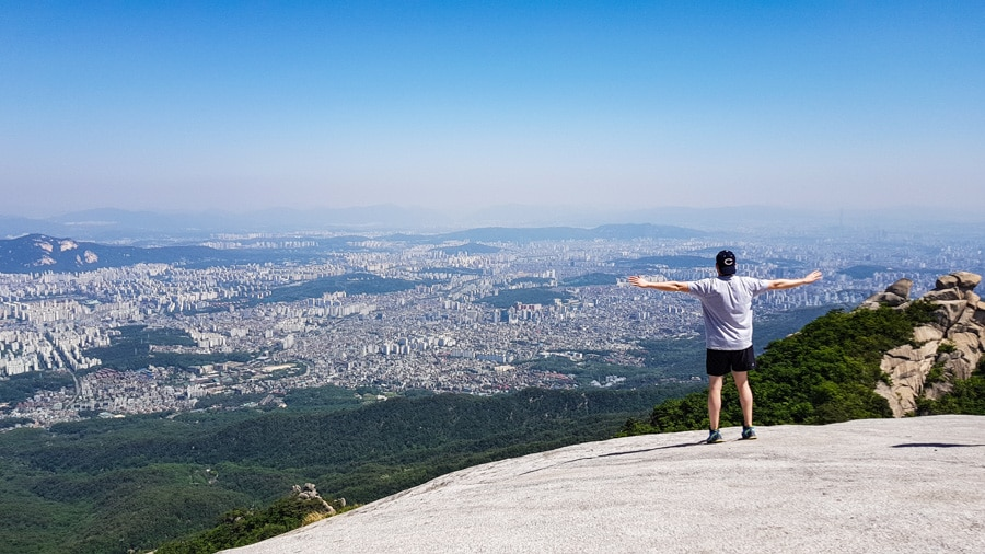 A man standing on a rocky outcrop in Bukhansan National Park overlooking Seoul