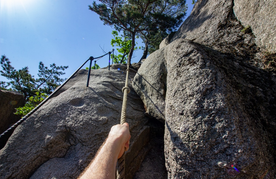 A hand grabbing a rope leading up the mountain