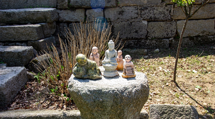 Buddha images and statues on a small pedestal outside a temple in Bukhansan National Park